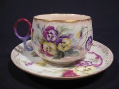 Limoges Hand Painted Pansies Flower Cup and Saucer Dainty, hand-painted porcelain cup and saucer is in very good condition. Moderate loss of gold accent to rim and handle. Shipping to USA = $10.50. C