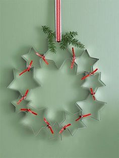 Cute kitchen wreath-star cookie cutters, silver paper clips, and red twist ties. On a flat surface, arrange cutters into a circular shape as shown; clip together where stars touch. Carefully flip wreath over and secure the same spots with additional paper clips. Tightly twist ties around these sections as shown. Evergreen sprig optional