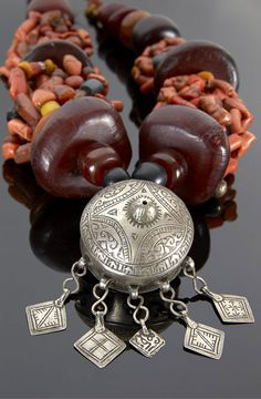 Necklace detail; coral, copal amber, stone beads and a central silver pendant, Morocco.