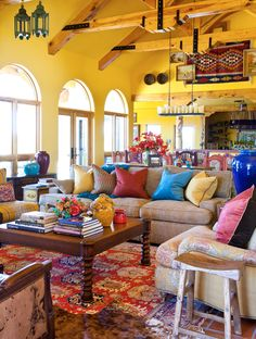 Warm golden yellow provides background for living room filled w/ pops of color, texture & decorative elements