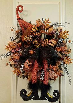 She is ready to cast a spell on you....and shes no ordinary witch   If you are looking for that traditional Halloween colors of orange and black , well this wreath is for you. Big and full with premium wired ribbon that can be reshaped when those Oct winds start to blow. A beautiful witch hat and matching legs with a shirt will conjure up and spell for your little trick or treaters. Hat and legs are made with an orange and spider pattern. Her boots are full of glitter and her skirt even…