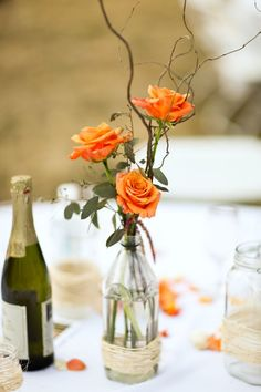 Understated centerpieces for a casual gathering.... ie: Old bottles, then the  bottom wrapped in twine or string or raffia, & then 3 open roses in the bottles, with tiny branches and leaves.