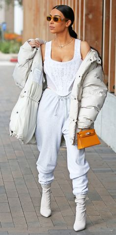 Kardashian stepped out in L.A. in an all-white look, featuring a lacey tank, baggy sweats, and an oversize puffer coat (try a similar look via nordstrom.com). A mini Birkin bag and matching orange sunnies completed her look.