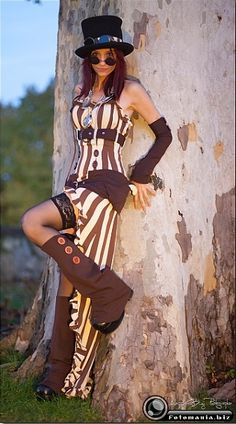 Deep in the Forrest, Steampunk fashion still makes a head to toe statement. Top hat & a manipulative look over the frame of her monicals, she wears the classic bold stripe, this time in ivory & chocolate in this long, sexy dress with a ruffled high/low hemline, lace trimmed stockings & heavy chocolate boot covers.