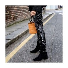 WELL HEELED: Known for its sculptural shapes with a glam-rock feel, #Dorateymur's shoes are favorites of street style icons. Set on an angled block heel, these 'Nizip' boots are made from velvety black suede and pierced with an oversized silver hoop.