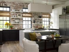 Exposed brick in kitchen - love the mix of black cabinets, open shelves, industrial windows, and white marble counters.