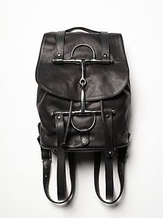 An American made take on the conventional backpack, with its supple pebbled leather and equestrian elements. Perfect for everyday wear with stainless steel horse bit and draped straps that assimilate a horse's reins, adding extra flair. Features stainless steel full cheek D-Ring bit at front of bag with two adjustable straps and top handle. Drawstring closure with magnetic closure on bag's flap. Lined interior with two bucket pockets and single zip pocket. Metal feet protect base.