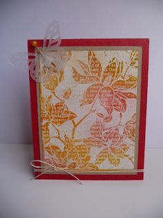 "By Patscrap. Stamp Hero Arts ""Large Blossom""(a negative image stamp) in VersaMark on white cardstock; heat emboss with clear powder. Stamp text over the piece in VersaMark; heat emboss with white powder. Sponge red, yellow, and orange Distress inks over piece; buff to remove excess ink. Layer on kraft mat then red card base. Add die-cut butterfly, twine, and pearl."
