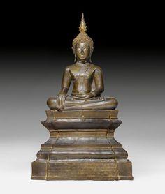 BUDDHA SHAKYAMUNI. Laos, ca. 16. Jh. H 93 cm. Bronze mit dunklem Glanz. Der historische Buddha sitzt in Maravijaya-Position auf einem mehrfach getreppten Thronsockel mit leicht ausschwingenden Ecken. Stachelige Noppenlocken bedecken das Haupt, die Ketumala ist abnehmbar. Ein freundliches Lächeln erhellt das Gesicht. Stifter-Inschrift am Sockel in Pali und Tham (laotische Schrift für buddhistische Texte).