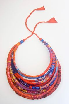 Lovely necklace made from wrapping fabric scraps around cotton cord and binding the fabric in place with colorful thread.
