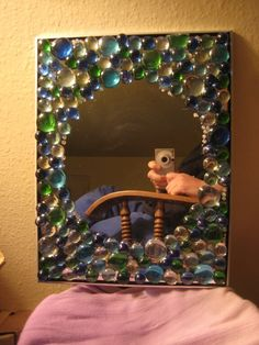 Flat and round marble mirror. Cost: a little less than $2.00. New mirror at the dollar store, and a bag of marbles also from the dollar store and lots of hot glue.