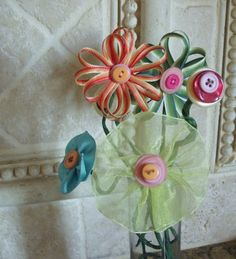 These are flowers made from ribbon and buttons. I think they would make embellishments for hairclips or headbands.
