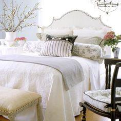 Soft wall color, curvy headboard & chandelier spell romance