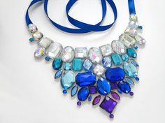 Bright royal blue, baby blue, aqua crystal AB (aurora borealis/ rainbow coated) and dark purple rhinestone jewels decorate this sparkling bib necklace. I wanted to create an elegant bib necklace that variegated from bright blues to a deep royal purple. A hint of crystal AB stones add contrast and...