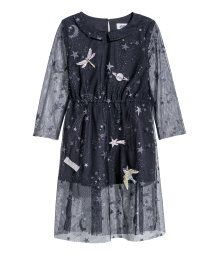 Long-sleeved dress in airy mesh with a printed design appliqués. Rounded collar at front, opening at back of neck with button, and an elasticized seam at waist. Raw edges at cuffs and hem. Partly lined.