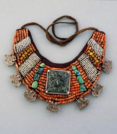 """""""Woman's gorget (neck ornament); the attached silver pendants have the shape of stylised tiger-claws for the protection of the wearer. India, Ladakh; early 20th c."""" The materials are described as """"coral, seed pearl, amber and turquoise beads and a silver and turquoise ga'u, silver pendants, textile."""""""