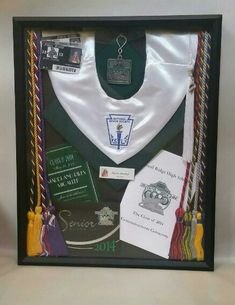 Graduation Shadow Box with cords, cap, invitations, program, tassel, and student id's from each year.
