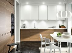 The intigrated kitchen. A kitchen with walnut effect doors, white accent doors and white worktop. Combined with stainless steel extractor hood, dark grey oven and microwave oven.