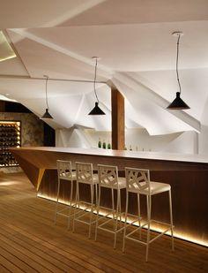 Nosotros Bar aménagé avec un meuble bar design en bois, chaises de bar blanches, suspensions noires et cave à vin moderne