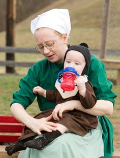 Emma Miller holds her son during a farewell picnic outside the schoolhouse in Bergholz, Ohio, April 9, 2013.