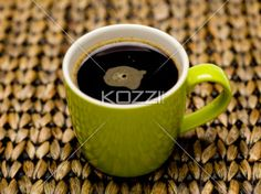 hot coffee in green mug - A cup pf coffee on a wicker place mat.