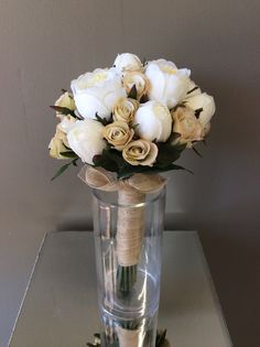 An artificial silk posy bridal wedding bouquet of white peonies and off cream spray roses wrapped in a jute hessian ribbon