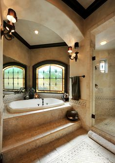 Hacienda bathroom with glass shower, corner tub. This whole house is AMAZING.