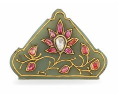 A GEM-SET JADE PENDANT  NORTH INDIA OR DECCAN, 19TH CENTURY  Of triangular form with rounded points, decorated with a large seven-petalled flower set with foiled red gemstones, the gold stems leading to gem-set floral buds, outlined in gold, drilled at top 2 5/8in. (6.7cm.) across