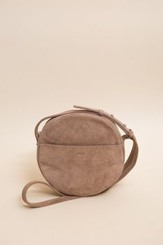 A simple geometric cross body bag from Baggu, in dune suede. Adjustable strap for over the shoulder or cross body use. Exterior pocket and two interior pockets. Fully lined. - 8.5 in. H x 8.5 in. W x