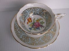 "Vintage Royal Stafford English bone china matching cup and saucer, pattern No.1814.  Cup is 4"" across rim, and saucer is 5 &1/2"".  Scallop edging with gold trim, rose & tulip plus assorted wild flowers inside cup with pale blue & delicate gold design edging on white background.  This set was acqu..."