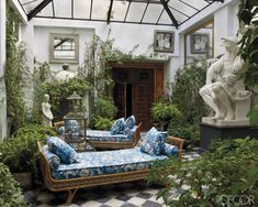 In the courtyard of this Madrid home decorated by Lorenzo Castillo, 1960s Jansen daybeds are upholstered in a Madeleine Castaing fabric, the cast of a Michelangelo sculpture is from a Paris flea market, and the Gothic Revival doors are 19th-century Spanish.