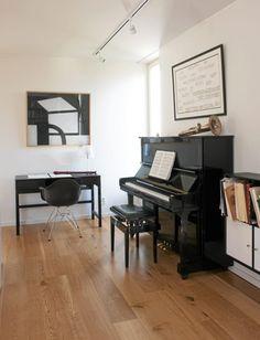Over pianoet henger et partitur av karlheinz Stockhausen, over notebordet en tegning av Bertil Greging i kull og kritt, med spennende lysspill.