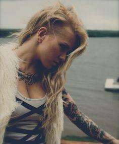 Cette coiffure est très tendance, puisqu'on remarque que les longs cheveux de cette femme ont été rasés d'un côté, au-dessus de l'oreille. Le reste de sa chevelure blonde a été séparée par une raie sur le côté et descend librement sur sa poitrine en de belles ondulations.