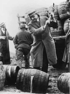 After the passage of the 18th Amendment and the Volstead Act in 1919, the making and selling of alcohol was illegal. This federal policeman uses a pickax to destroy a rum-runner's cargo in San Francisco during Prohibition.