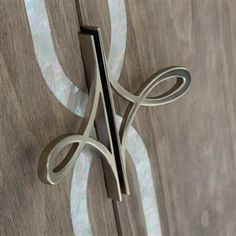 Straight Up with a Twist. Each door is banded in white Mother of Pearl and custom designed door pulls, both featuring a scroll motif that is carried through to the metal stretcher uniting its slim legs. Cabinet And Drawer Knobs, Knobs And Handles, Knobs And Pulls, Door Handles, Door Pulls, Kitchen Handles, Drawer Pulls, Cabinet Hardware, Caracole Furniture