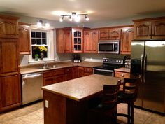 Grey walls, stainless steel appliances and wood cabinets with medium stain. Yellow flowers lighten up the kitchen! #kitchen #grey