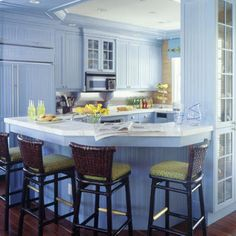 Upbeat Design    Blue beaded-board walls and cabinet are cheerful counterpoints to the rich, chocolate-brown hardwood flooring and barstools. The chairs' woven-leather backs add rustic sophistication, while lime-green fabric with blue accents adorns seat cushions.