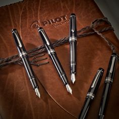 Pilot Custom 912 fountain pens atop a gorgeous custom leather notebook