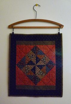 *** What a great idea for hanging! Mini quilt displayed on wooden clothes hanger. Hanging Quilts, Quilted Wall Hangings, Small Quilts, Mini Quilts, Quilting Projects, Quilting Designs, Quilt Wall Hangers, Skinny Quilts, Quilt Display