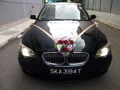 BMW mit goldener Band und roten Rosen dekoriert