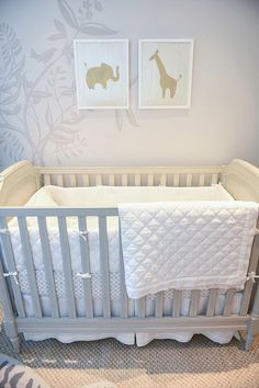 Chic nursery features  a gray wall accented with a tree mural lined with a gray crib, Pottery Barn Kids Blythe Crib, placed under an elephant and giraffe art print.