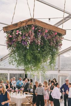 Boho wedding inspiration with a large hanging floral chandelier, featuring green, pink and lilac flowers. This is beautiful wedding inspiration for luxury country weddings.