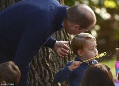 George plays with bubbles as his father Prince William looks on during the children's tea ...