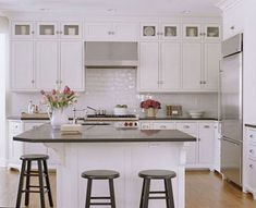 White Vintage Kitchen Textured white subway tiles line this charming kitchen's backsplash, giving the room a light, spacious backdrop. The L-shape island provides separate areas for eating and prep work. Now the space is perfect for both day-to-day family life and entertaining.