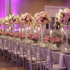 Vases hauts et vases bas alternés pour une ambiance très symétrique et solennelle adoucie par la présence de bougies et la couleur des fleurs, hortensias, orchidées et roses. Les chaises et la table recouverte de nappe et de serviettes mauves ajoutent au côté romantique de la réception.