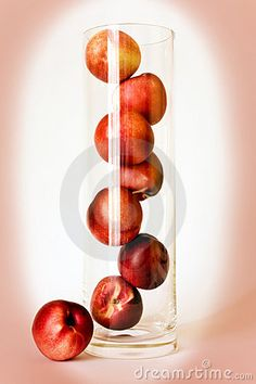 A tall glass vase used to display fresh, whole nectarines.