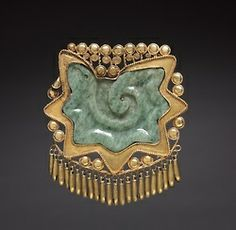 Pectoral Ornament  c. 1200-1519  Mixtec or Aztec        This extraordinary pendant consists of a conch shell section carved in jade, enclosed in a delicate gold frame with tiny dangling bells. This symbol was worn by the deity Quetzalcoatl (Feathered Serpent) a culture hero credited in one myth with creating human life by sprinkling his blood on ground bones. The pectoral may have been worn by a priest, or by a ceremonial impersonator of Quetzalcoatl.