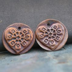 """Handmade Embosse Stylized Squash Blossom Heart Rounds. All pieces are torched to bring out some of the hidden color within the copper and sealed to protect. Each piece measures 11/16"""" in diameter with 1 jumpring hole at the top."""