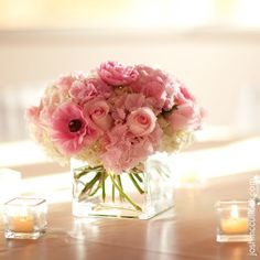 Pink roses, ranuculus, and hydrangeas in a clear glass square vase