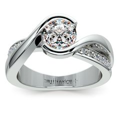 Twenty round cut diamonds are pave set in this elegant half bezel diamond bridge engagement ring in platinum, accenting your choice of center diamond. Approximately 1/4 carat total weight and proudly made in the USA.